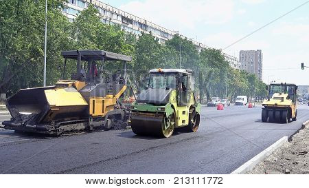 Road construction. Applying new hot asphalt using road construction machinery and power industrial tools. Roadworks repaving process.