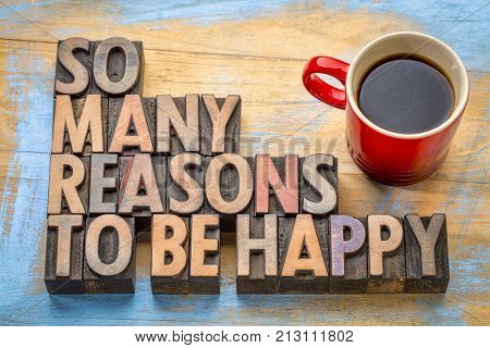 So many reasons to be happy word abstract in vintage letterpress wood type with a cup of coffee