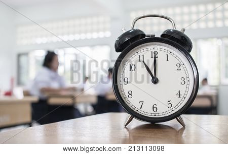 Closeup of Retro alarm clock with ten o'clock on table teacher in blur students exams classroom. Time is indefinite continued progress of existence. Education concept selective focus.