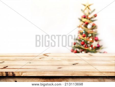 Christmas and New year background with empty wooden deck table over christmas tree and blurred light bokeh. Empty display for product montage. Xmas background.