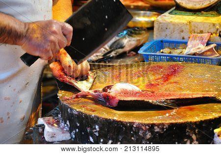 HONG KONG - OCT 25, 2013 - Fishmonger slicing up a fish at a Hong Kong wet market
