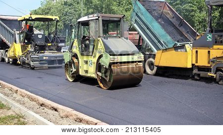 Kiev, Ukraine - June 19, 2017: Road construction. Applying new hot asphalt using road construction machinery and power industrial tools. Roadworks repaving process.