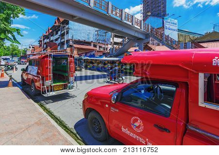CHIANG MAI THAILAND - JULY 27: Red taxis waiting for people in the downtown area of Chiang mai on July 27 2017 in Chiang Mai