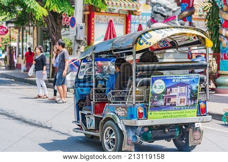 CHIANG MAI THAILAND - JULY 29: Tuk tuk driving down a road in the downtown area of Chiang Mai July 29 2017 in Chiang Mai