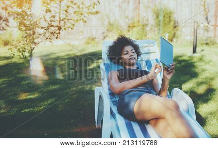 Beautiful young black female with curly African hair is laying on the striped daybed in the city park and browsing net using digital tablet with copy space place for advertising your logo or text