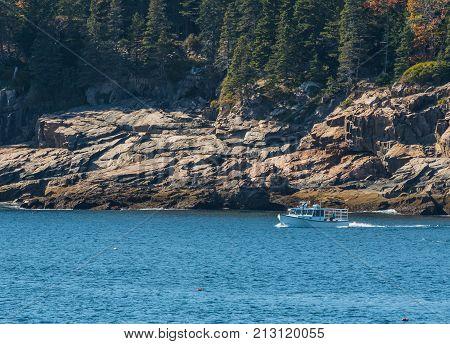 White Lobster Boat Along Rocky Maine Coast checks traps