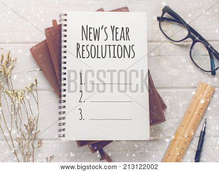 Notebook with New's Year Resolutions massage glasses and working ornament on white wooden table background.