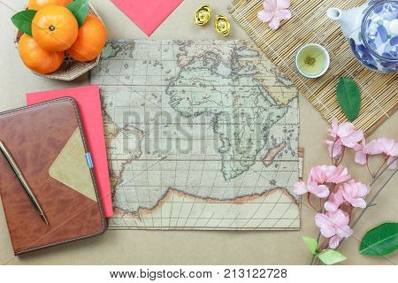 Top view aerial image of plan to travel on Chinese New Year & Lunar New Year holidays concept background.several objects on modern design brown wood at home office desk.Essential accessories for trip.