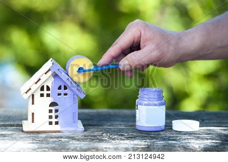 Hand with brush paints a toy house in lavender color the background is a green garden. Housing construction building painting home improvement home renovation apartment renovation creation