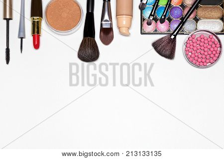 Make-up products background. Liquid foundation, loose powder, eyeliner, mascara, eyeshadow, blush, lipstick, basic brushes. Makeup must haves for modern woman. Copy space