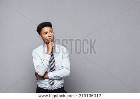 Business Concept - Confident Thoughtful Young African American Holding Hand On His Chin And Thinking