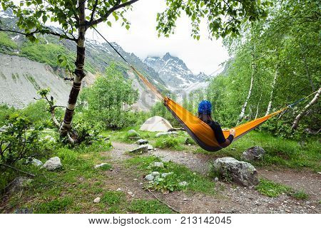 Woman traveler relaxing in hammock on a green meadow in the mountain gorge next to glacier and admiring beautiful view. Camp with magic view. Wide angle back view. Glacier Chaladi Svaneti Georgia.