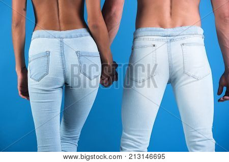 Seductive couple jeans wearing which accentuate beautiful form. Man holds a woman by hand tenderness and harmony in relationship. Ass and buttocks of couple in love. Sexy naked back denim trousers