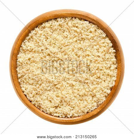 Ground walnuts in wooden bowl. Walnut meal, used in bakery. Grounded kernels, the seeds of the common walnut tree, Juglans regia. Isolated macro food photo close up from above on white background.