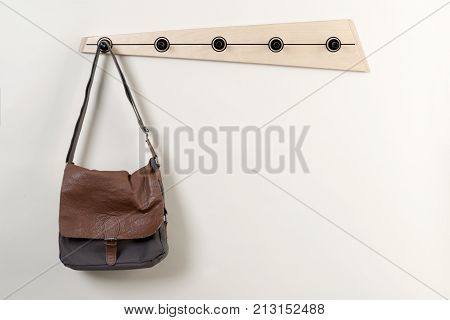 Satchel Hanging On A Wooden Wall Coat Rack