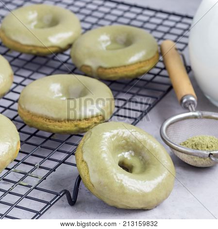 Freshly baked matcha banana donuts with matcha citrus glaze on a cooling rack square format