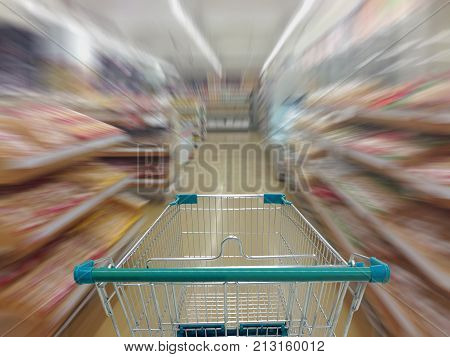 Supermarket aisle with empty shopping cart Supermarket store abstract blurred background with shopping cart.