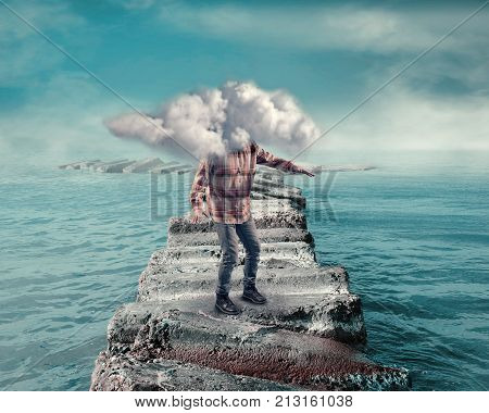 Young man covered by a cloud walking on a pontoon of rocks in the ocean.