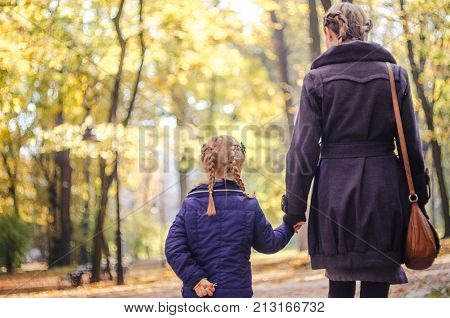 Mother with daughter walking in the park in autumn holding hands. Yellow leaves on tress. Back view