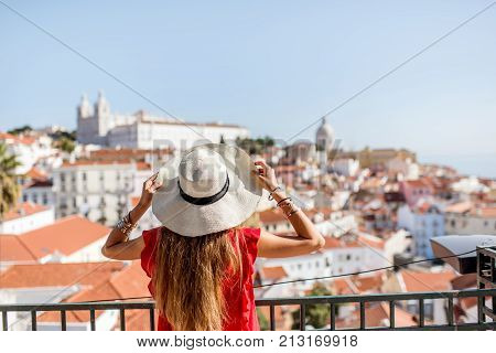 Young woman tourist enjoying beautiful cityscape view on the Alfama region of Lisbon city during the morning light in Portugal