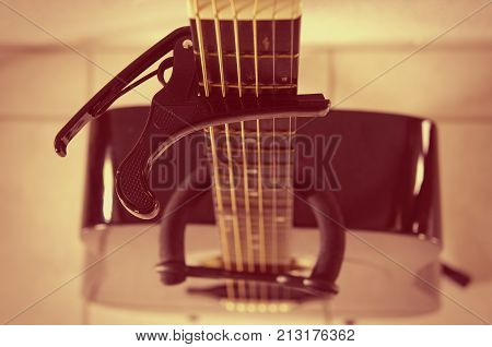 acoustic guitar with capo on a fingerboard
