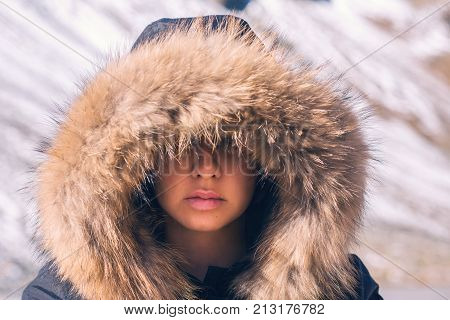 Beautiful girl in a hood with fur of a winter jacket. The girl's face is hidden in a hood with fur.