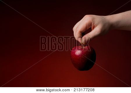 A Hand giving an apple isolated on a christmas red background. Compassion and generosity concept.