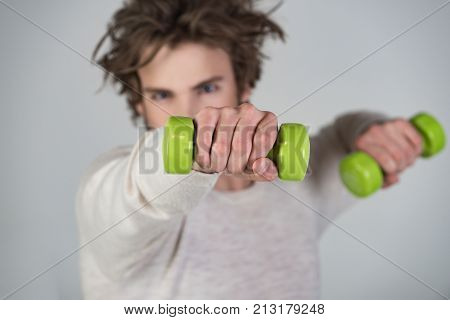 Guy is training with light green dumbbells in the gym on gray background in white T-shirt with unkempt hair. Young athlete blurred in focus hand with dumbbell. Health and good ideal figure