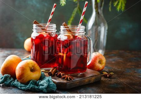 Two glass jars with a hot Christmas drink made from cranberries and apples with spices mulled wine punch or grog.