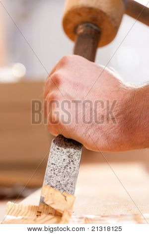 Carpenter working with a chisel and hammer in his workshop; close-up on chisel