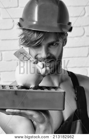 young handsome bearded macho man smiling builder with sexy muscular athletic strong body has strong hands in orange hard hat or helmet holds pig dollar moneybox and brick on white wall background