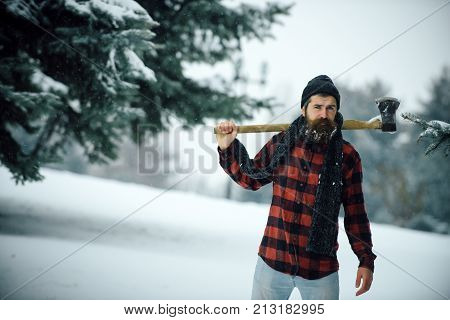 Man with beard in winter forest with snow hold axe. Christmas hipster lumberjack with ax in wood.. Wanderlust hiking and travel. New year man in snowy cold forest. Winter holiday and celebration.
