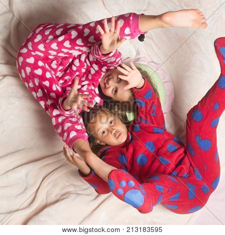 Children in pajamas have fun in bed top view. Happy childhood family love friendship. Girl nightwear fashion. Bedtime slumber dream sleepover. Comfort home concept.