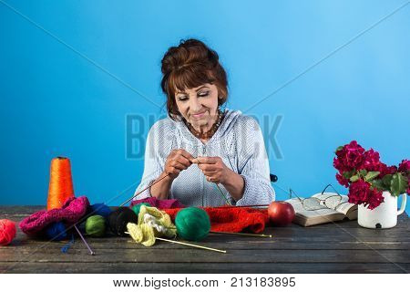 Old Woman Knitting Socks From Colorful Thread