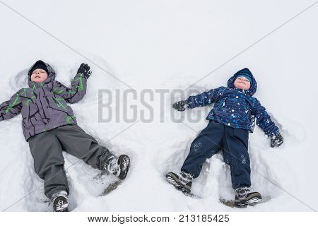Two Little Siblings Kid Boys In Colorful Winter Clothes Making Snow Angel, Laying Down On . Active O