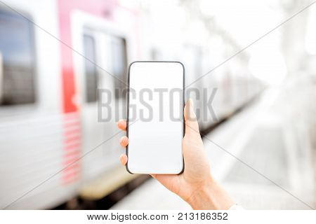 Holding a smarphone with empty screen with train on the background at the railway station