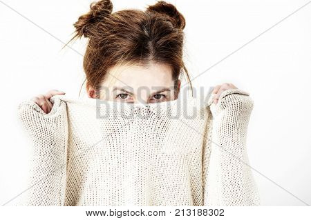 Funny cute young woman is smiling into the camera while covering her face with the collar of her sweater. Lifestyle concept.