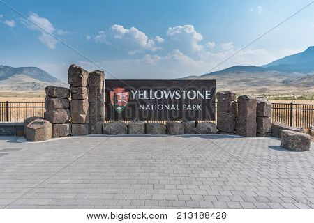 Yellowstone National Park United States: August 5 2017: Yellowstone National Park Sign with rollling mountains in background