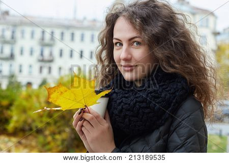 Charming stylish Caucasian student lady with pleasant cheerful smile sitting outside enjoying fresh autumn weather. Beautiful European woman drinking hot take away coffee with maple leave in hands.