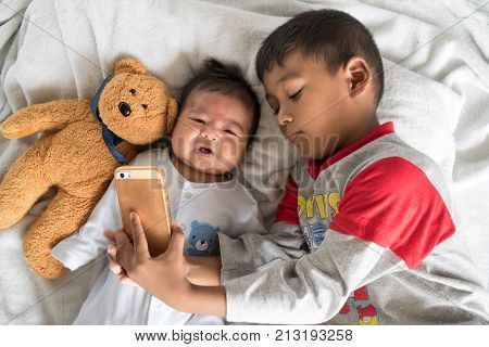 Cute Little Brother Using Mobile Taking Selfie With His Brother