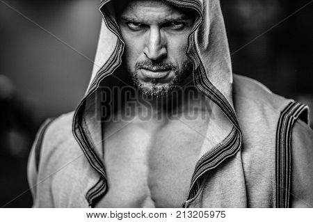 Brutal handsome Caucasian bodybuilder working out in the gym training chest pumping up pectoral muscles withdumbbells and on crossovers gaining weight and poses fitness and bodybuilding concept