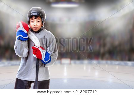 Junior hockey player posing on ice in sports arena. Shallow depth of field on background and copy space.
