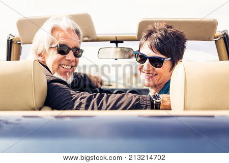 outdoor portrait of a modern senior couple driving a convertible classic car.
