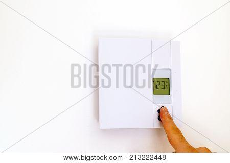Finger adjusting thermostat in house in celcius