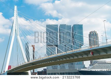 Passenger ship moored under gently arching shape of Erasmus Bridge with architecturally modern De Rotterdam towers above in Rotterdam Holland.