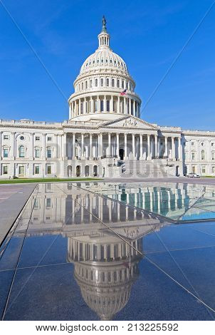 The United States Capitol monument with dome reflection in the morning. The building sits atop Capitol Hill at the eastern end of National Mall in US capital.