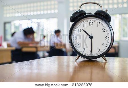Closeup of Retro alarm clock with ten o'clock on table teacher in blur students exams classroom.