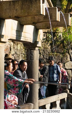 KYOTO JAPAN - APRIL 28 : Tourist collecting water from the Otowa-no-taki waterfall ( for health longevity and success) at Kiyomizu temple on April 28 2017 in Kyoto Japan