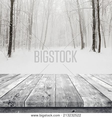Wooden table over winter snow covered forest. Beauty nature background