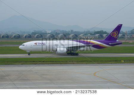 HANOI, VIETNAM - JANUARY 12, 2016: Airplane Boeing 777-2D7 (HS-TJW) Thai Airways International on the taxiway of Noi Bai Airport